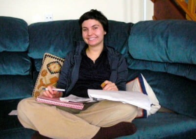 Natalie sitting on the couch with a notebook and pen, takes a break to smile at the camera
