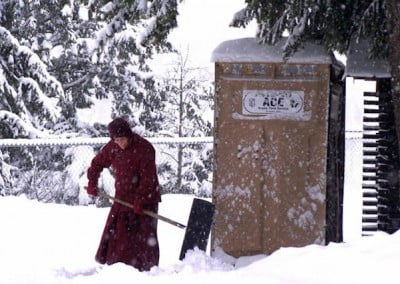Venerable Semkye shovels snow so the retreatants can get to the porta potty in winter.