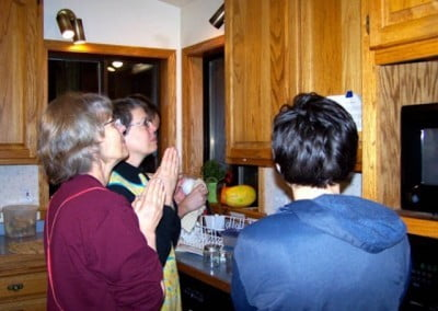 Volunteers stand together in the kitchen and recite the lunch prep prayer