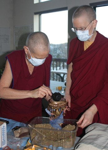 Venerable Chodron and Venerable Tarpa scoop some of the incense and juniper powder to fill in between the mantra rolls. The masks are to prevent us from breathing on the statues.