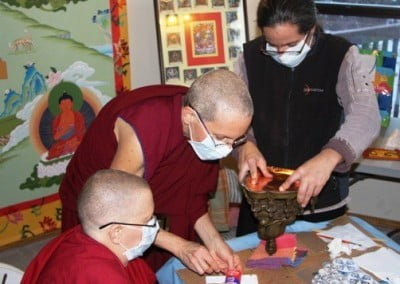 Venerable Jigme, Venerable Semkye and Rachel use epoxy, a still hand, and gentle pressure to make sure the base is airtight.