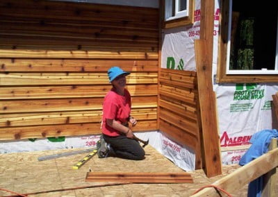 woman putting up siding on cabin