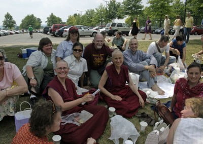 The Abbey community and lay guests sit on the ground outside and eat a picnic lunch