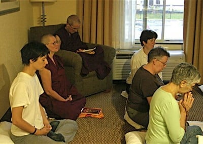 A group gathered sitting in a hotel room for meditation