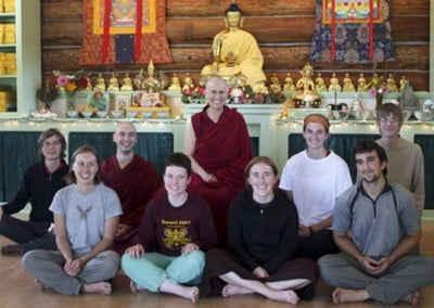 The group poses with the Buddha and Venerable Chodron.