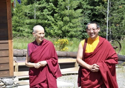 Venerable Chodron escorts Lama Lekshe into Ananda Hall after the group pays their respects to the Buddha.