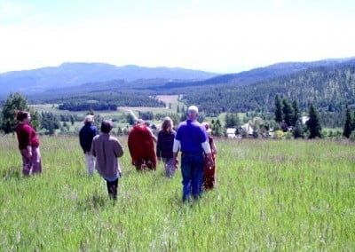 Residents and guests walk with Khensur Rinpoche through the meadow