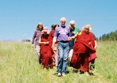 Residents and guests walk with Khensur Richpoche down the hill from the meadow.