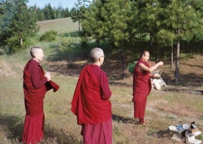Geshe-la tossing rice of auspiciousness in all directions.