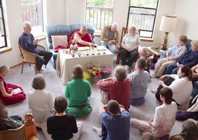 "During the puja. Jhampa Shaneman, the translator sits on a chair on the left. Harold and Vicki, the former owners came as well. They said, ""We're happy because you're happy"" in response to the Abbey purchasing their home. Harold is sitting on a chair to the right of Rinpoche. Vicki sits on the sofa, at the right."