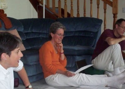 Three volunteers sit on the floor and one of them discusses notes from a piece of paper she is holding