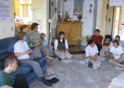 Volunteers sit on the floor and on a couch and discuss together