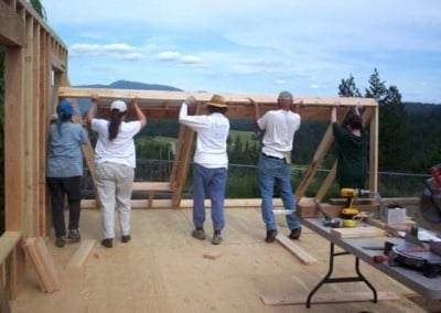 Five volunteer raise the framing in the cabin.