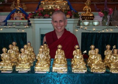 Venerable Chodron poses for a photo behind a table full of statues of arhats