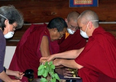 Three masked monastics and one lay volunteer gather materials on a table that will fill the statues