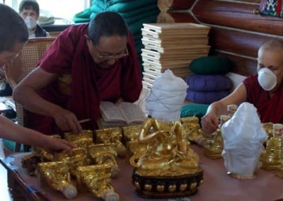 Buddhist monk leans over statues of arhats on a table that are laying flat