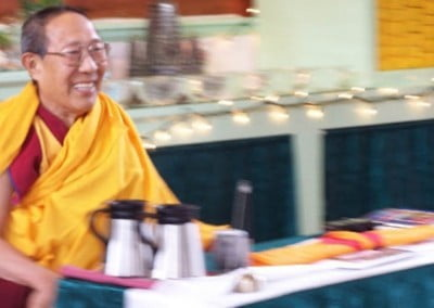 Panchen Otrul Rinpoche sits at the teachers table in the meditation hall