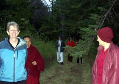 Venerable Chodron stands and looks back at some of the guests, allowing them to catch up as they walk through the Abbey forest
