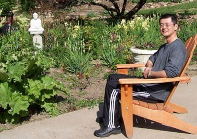 Yusuke, one of the Abbey's monthly offering service volunteers enjoys the garden with a Buddha statue donated by Venerable Lobsang last summer.