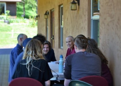 Venerable Chodron and young adults outside on a deck