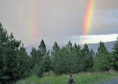 Person sitting a field looking at a double rainbow