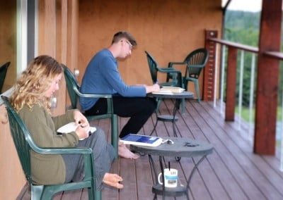 Two young adults studying on a deck