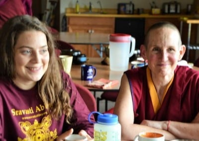 Smiling Venerable Tsepal and April at a dining table