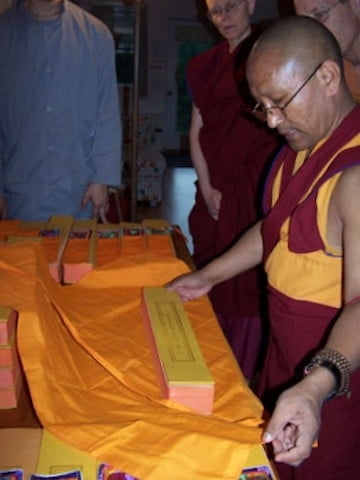A collection of Lama Tsong Khapa's <br> works arrives at the Abbey. Geshe-la and the residents work late into the night wrapping them. Here Geshe-la demonstrates the correct way to wrap the texts.