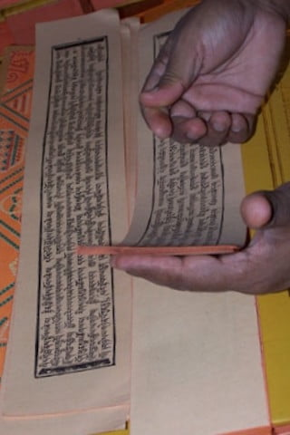 Delicate pages of the texts are carefully examined to insure their accuracy with the catalogue contained in each bundle.