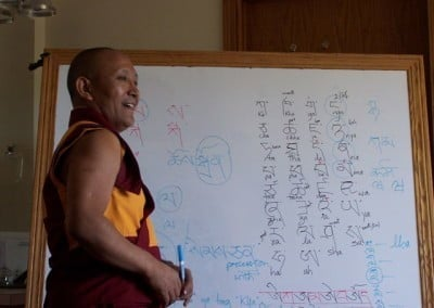 Geshe-la stands in front of a large white board and teaches the Abbey residents the fundamentals of the Tibetan language for five of the days he is with us.