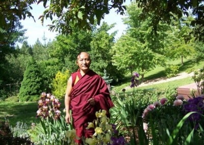 Geshe Dadul Namgyal standing in the Abbey garden.