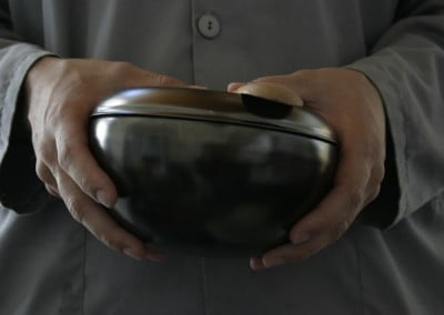 Closeup of an anagarika uniform and hands holding an alms bowl