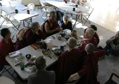 Monastics and guests sit around a dining room table