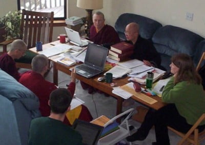 View from above of the four monastic working together at the table while a woman moderates and a man takes notes