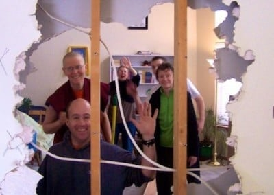 The group offering service waves to the camera through a hole in the drywall that they just made