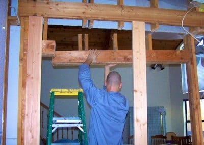 Jampel takes down the old header of the bearing wall, replacing it with a longer one.