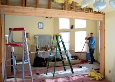 the old library full of ladder, drop cloths, and a volunteer working to transform it into the new dining room