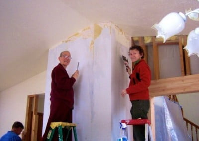 Venerable Semkye and Dallas strip off the old wallpaper in the kitchen. The wall will be textured and painted, which will make the room brighter.