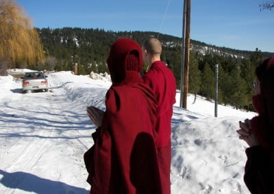 Two monastics watch as a car drives off on the snowy road