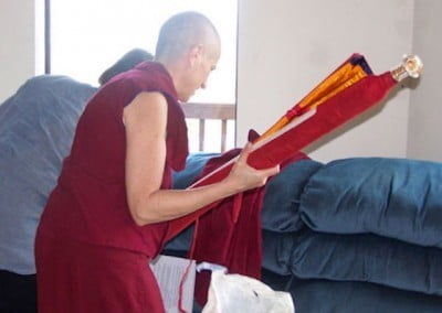Venerable Chodron opens a gift offered by Venerable Ghache to the Abbey.