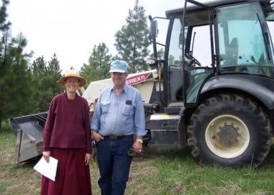 John Perry and Venerable Tarpa pose in front of a tractor