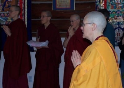Venerable Chonyi stands in the foreground, her hands in prayer, while monastic line the wall of the meditation hall beyond