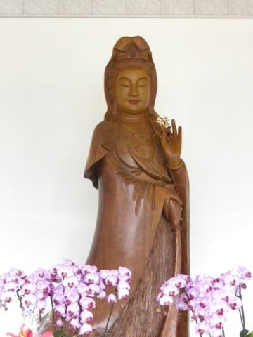 In a temple built just for her, an exquisite Kuan Yin statue carved from a huge tree trunk stands about 12 feet tall.