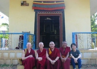 Four Buddhist monastics in robes sit on the step of a building with one lay person