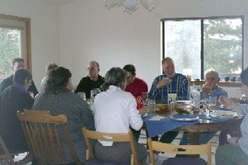 The volunteers sit down at the table and enjoy a meal together
