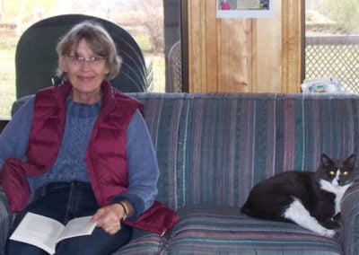 A woman studies on a couch with a cat laying beside her