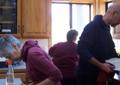 Three volunteers clean the kitchen