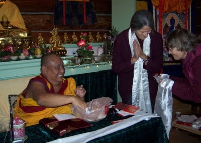 Nan and Sherran make offerings to Rinpoche in gratitude for his teachings. He gives each of them a blessing cord.