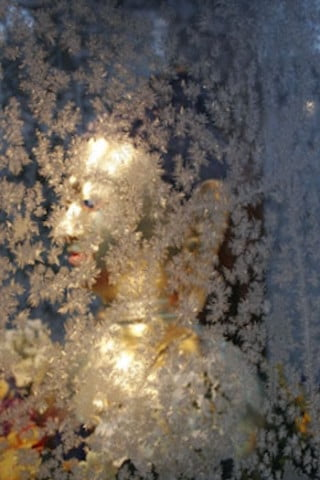 The Buddha garden statue shines brightly behind  the frosted window pane in the evening darkness.