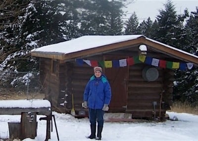 Sister Leslie, a Carmelite nun stands out side the Abbey's retreat cabin where she lived for the month. She was able to participate with the group as well as spend some quality time alone doing her own spiritual practice. She found the time with her Buddhist friends very fruitful.